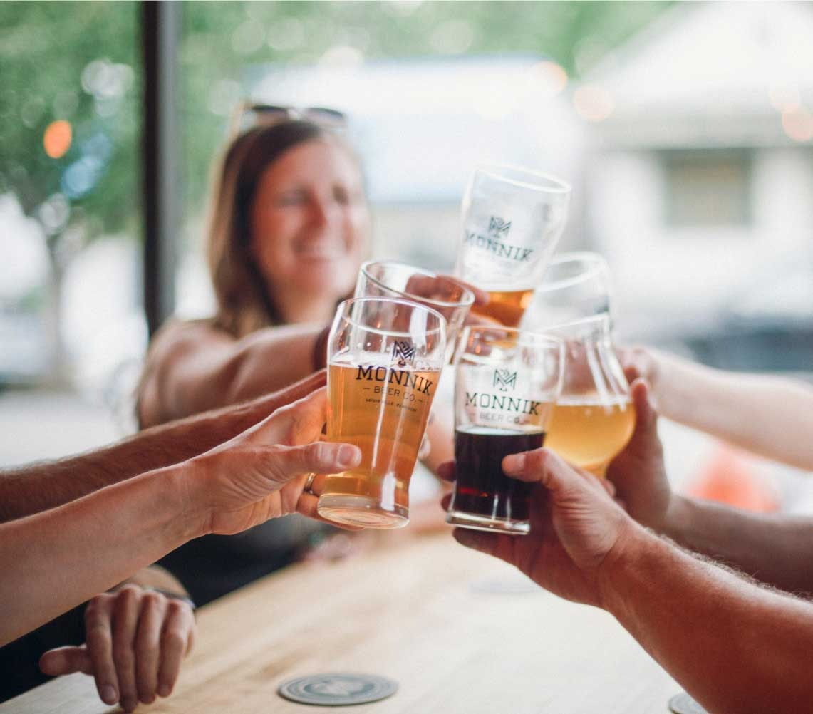 several people touching their beer glasses together