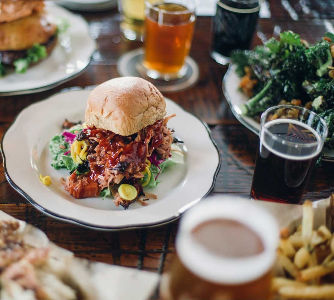 pulled pork sandwich on a plate surrounded by other foods and beers