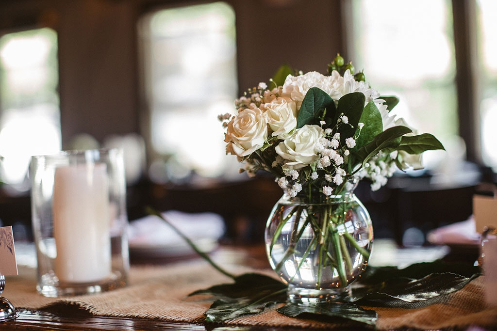 vase of flowers in the center of a dinner table