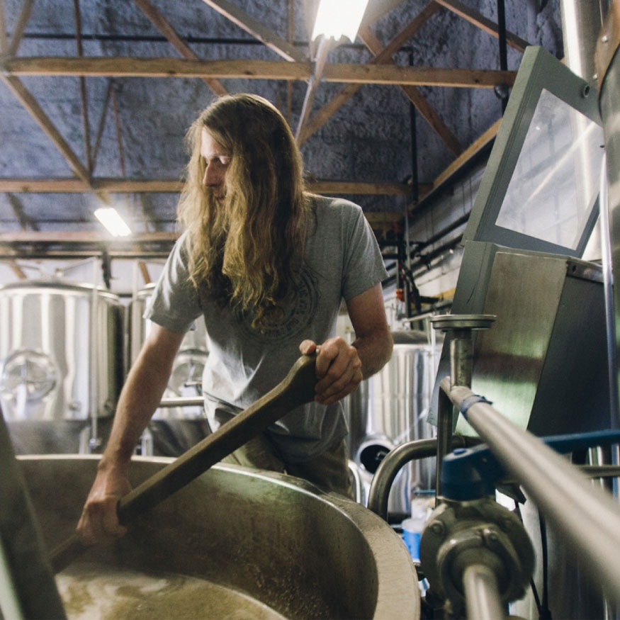 Scott Hand brewing and stirring beer